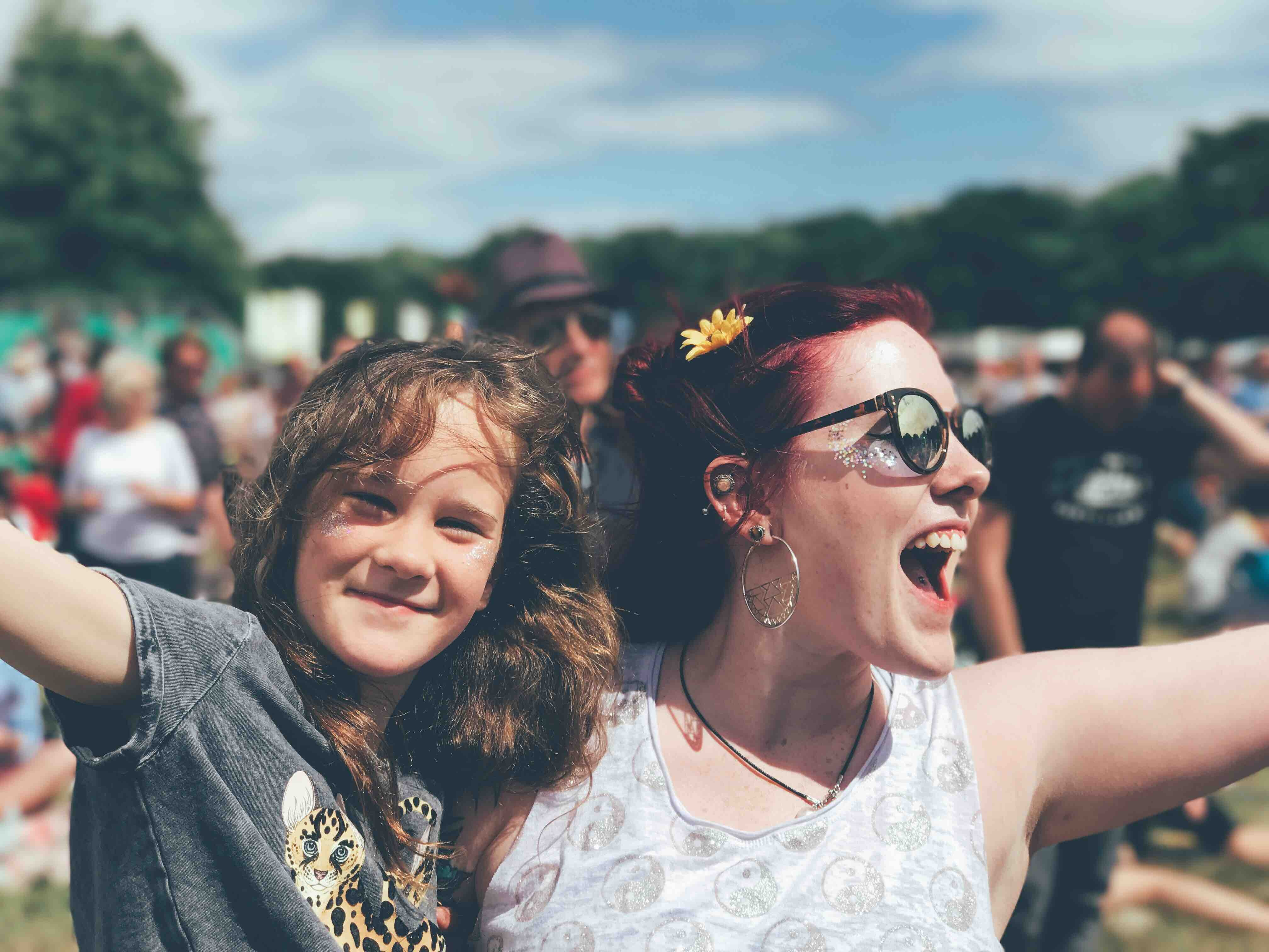 A woman and a young teen smile and wave in a field full of people. The woman has a tellow flower in her hair and glitter on her face. The child looks confident and content