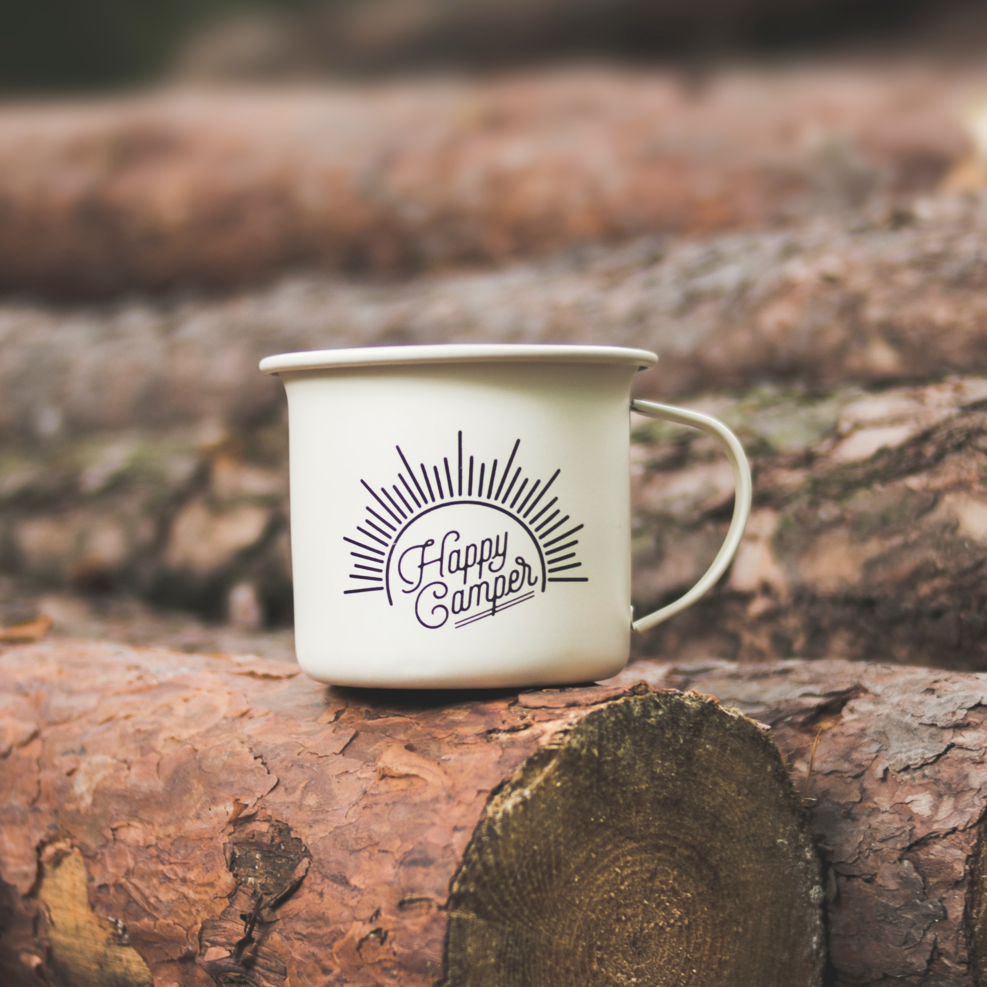 """An enamelled tin mug which reads """"happy camper"""" is resting on some logs"""