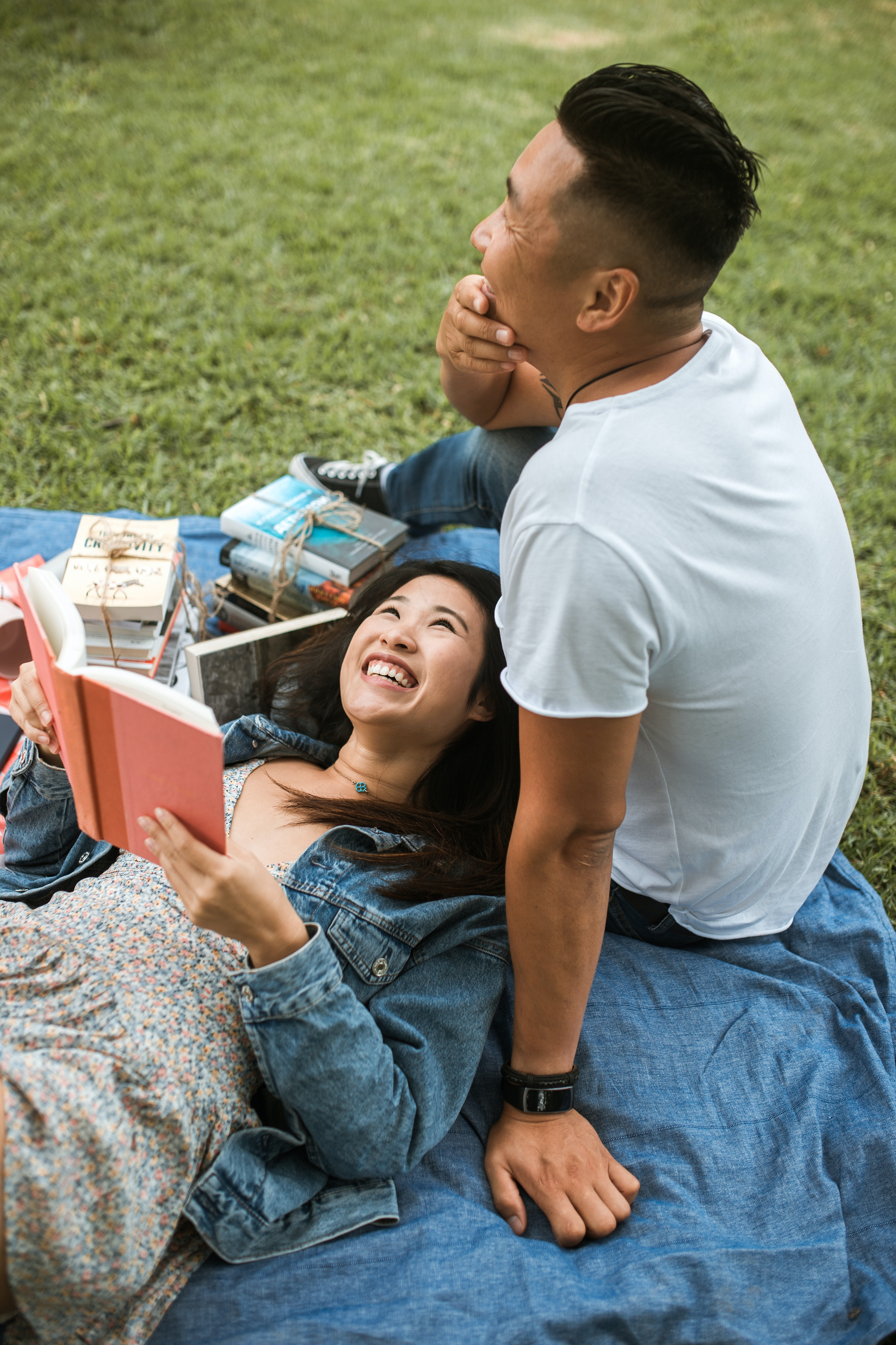 a man and a woman are lying on a picnic blanket. She is reading and looks happy, the man is looking into the distance, relaxed