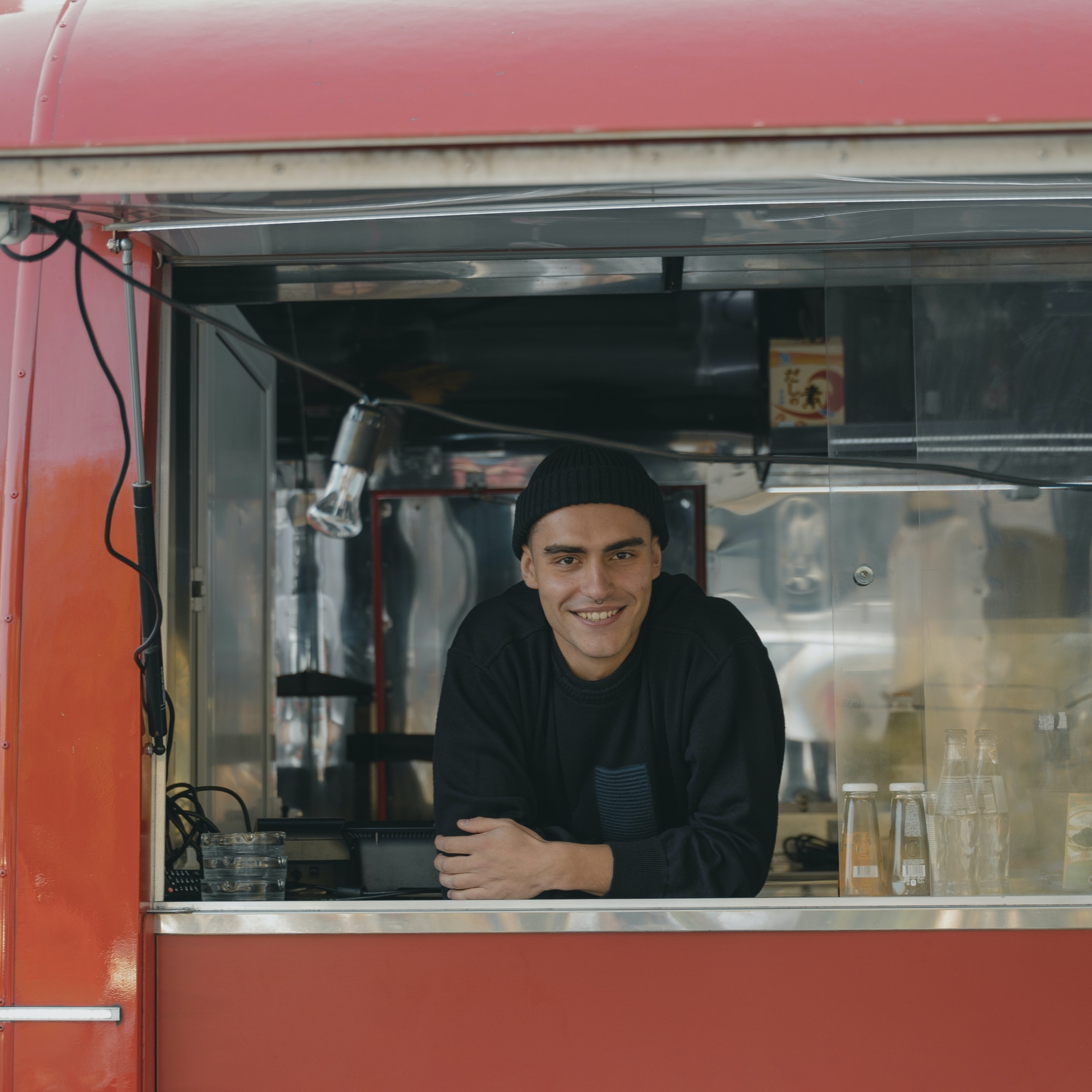 a smiling man leans out of the window of a food truck