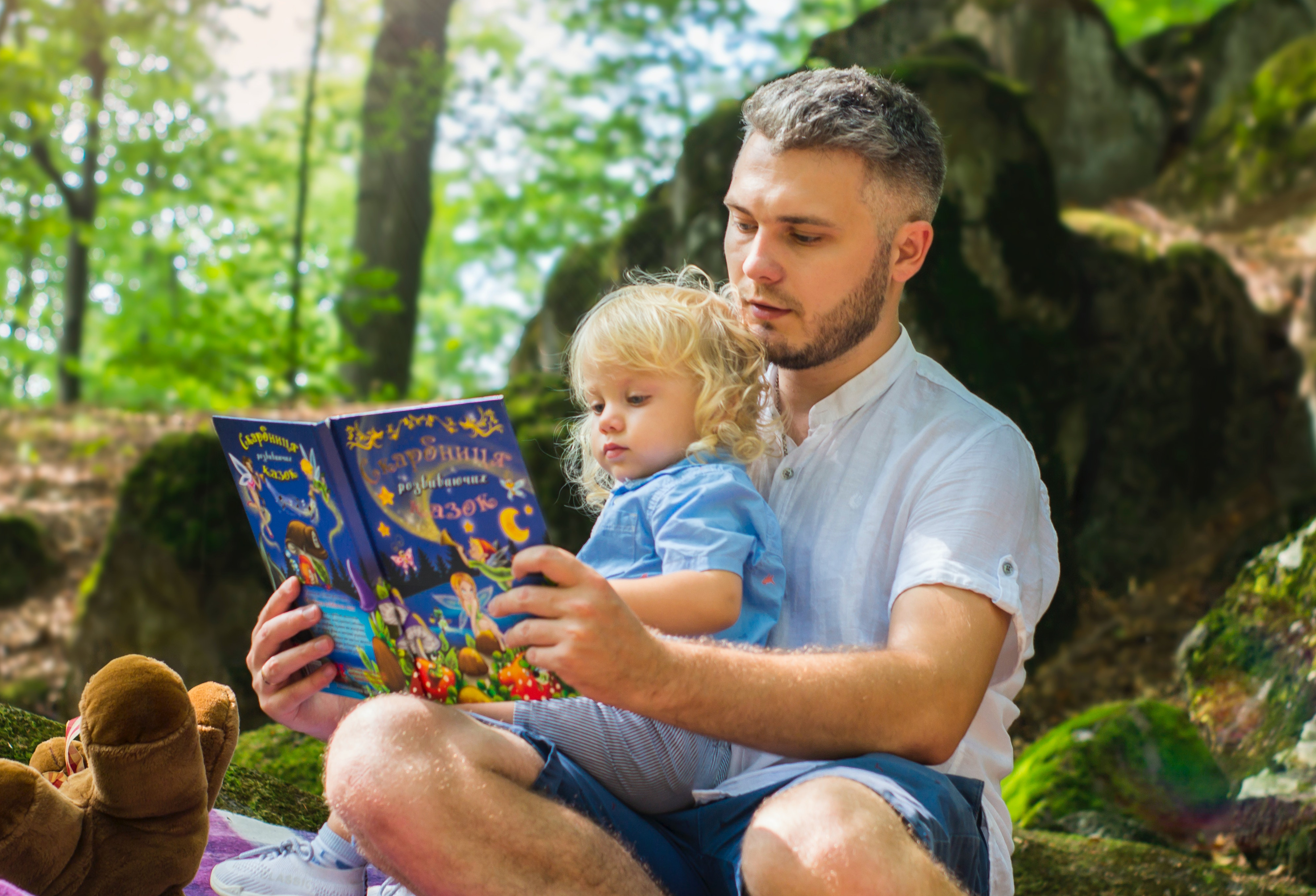 a man reads to a toddler outside in a sunny woodland